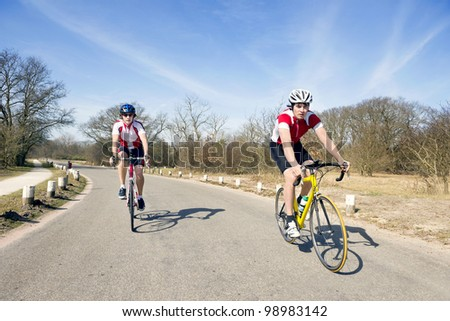Two cyclists on the road touring at speed - stock photo