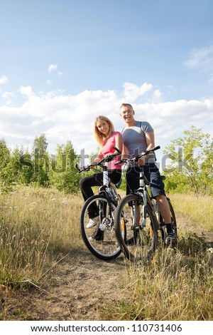 Two cyclists with bikes in the summer forest - stock photo