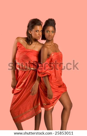 Two dark skinned sensual girls friends wearing Indian red traditional clothing - stock photo