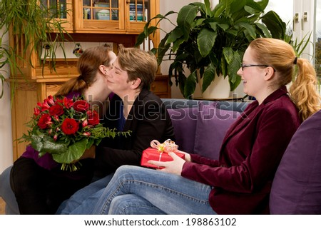 Two daughters congratulating her mother on her birthday with a present and a bouquet of red roses