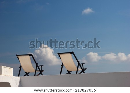 Two deck chairs on a roof against the blue sky. Sunny day  - stock photo