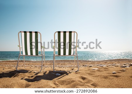 Two deckchairs on a pebbled beach, facing out to sea - stock photo