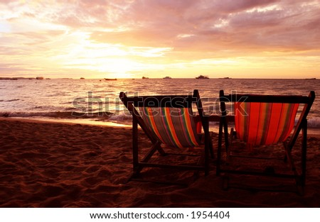 Two deckchairs on beach at sunset - stock photo