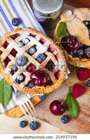 Two decorated homemade shortcrust pastry berry pies with striped cloth, shiny metal icing sugar shaker, fork and selection of berries on grunge style wooden table.   - stock photo