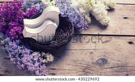 Two decorative birds in nest and  fresh aromatic lilac flowers  on vintage wooden planks. Selective focus. Place for text. Toned image. - stock photo
