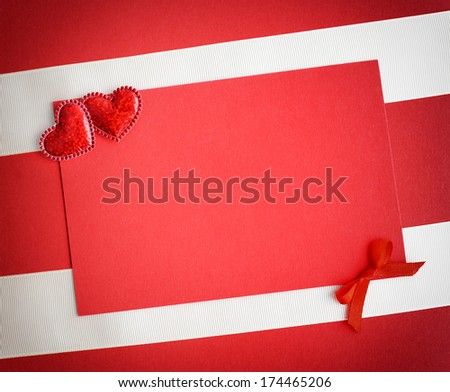 Two decorative hearts are on the sheet of red paper