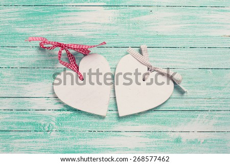 Two decorative hearts on turquoise painted wooden background. Place for text. Toned image. - stock photo