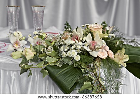 Two decorative wedding glasses with a bouquet of white orchids - stock photo