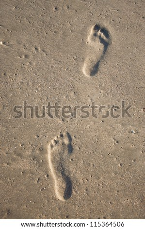 Two deep footprints of human feet on wet sand on the beach - stock photo