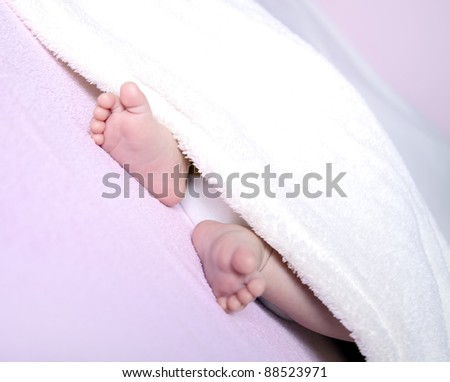 Two Delicate baby feet cover with beige blanket - stock photo