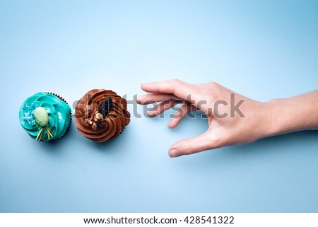Two delicious cupcakes with cream and hand on a blue background