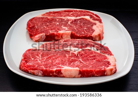 two delicious entrecote steaks on a white plate with dark wooden table in the background - stock photo