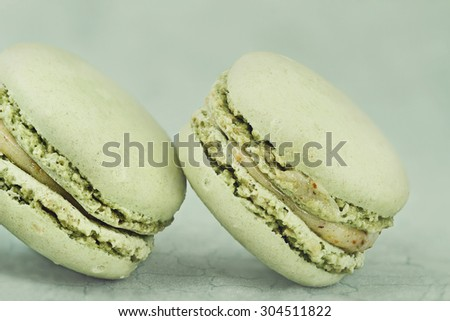 Two delicious green Pistachio flavored macarons with a vintage tone. Extreme shallow depth of field with selective focus on macarons. - stock photo