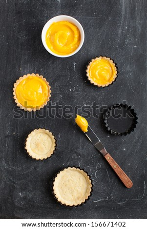 Two delicious homemade lemon curd tartlets and two cooked shortcrust pastry served with dish of lemon curd cream, taken from above on black chalky background with spatula. - stock photo