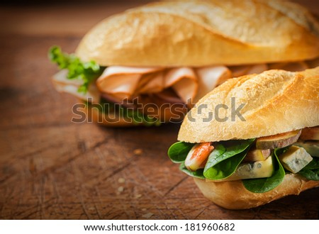 Two delicious savory rolls for a lunchtime snack on an old rustic wooden table with focus to the roll filled with cheese, fresh figs and spinach in the foreground,with copyspace - stock photo
