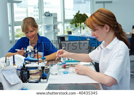 Two dental technicians working in a dental laboratory - stock photo