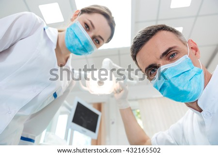 Two dentists making dental treatment to a patient in clinic - stock photo