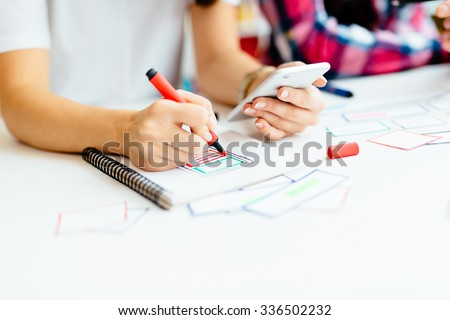 Two designers developing mobile application framework on notebook - stock photo
