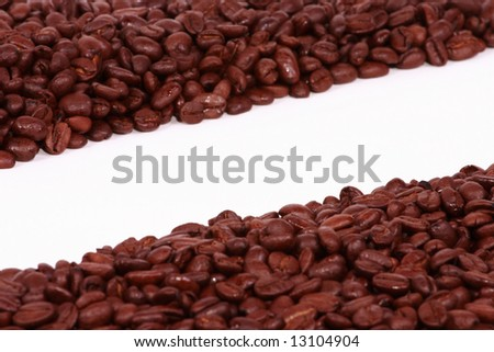 Two diangonal piles of coffee beans on a white background. - stock photo