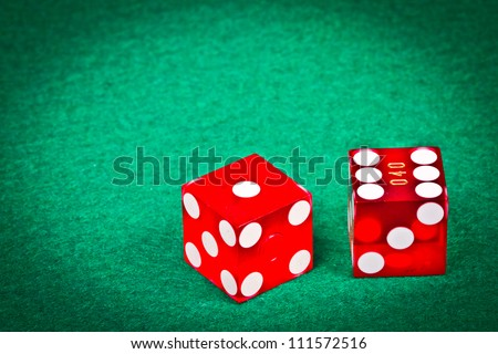 Two dices with seven over a green table - stock photo
