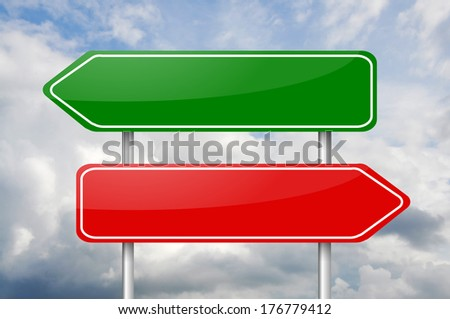 Two different direction arrow road signs red and green over the cloudy sky