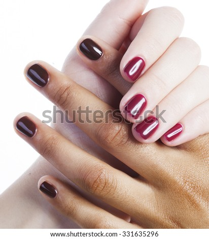 two different nathion manicured hands on white isolated, african with caucasian close up - stock photo