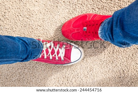 Two different pair of red shoes on the sand background - stock photo