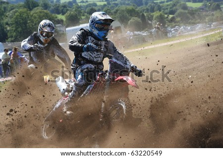 Two Dirt Bikes Battle a Corner - stock photo