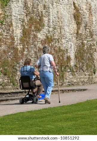 Two disabled females, one sitting on an electric mobility scooter and the other walking alongside with a walking stick. Grass lawn to the foreground and an old stone wall to the rear. - stock photo