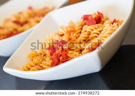 Two dishes of pasta spirals with salami, onions and tomatoes served white square dishes. - stock photo
