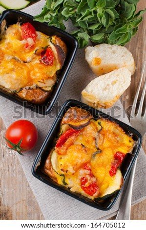 Two dishes of vegetable casserole with cheese, zucchini, cherry tomatoes and oregano on a rustic wooden board with vintage cutlery, home cooking