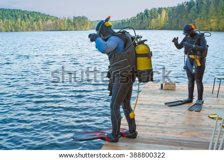 two divers going to jump into the forest lake - stock photo