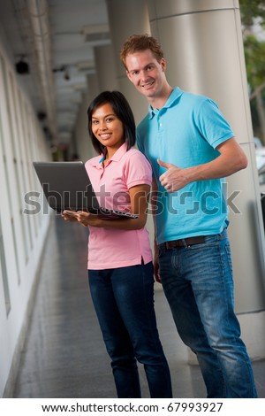 Two diverse college students standing in colorful blue, pink shirts holding laptop at university campus hallway. Female Asian Thai model of Chinese. Tall male caucasian British nationality thumbs up