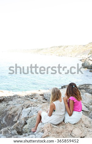 Two diverse friends, caucasian and african american teenager girls relaxing together on textured rocks contemplating the blue sea, outdoors nature. Healthy holiday travel lifestyle, beach exterior. - stock photo
