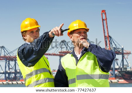 Two dockers in discussion, in front of a large industrial harbor - stock photo
