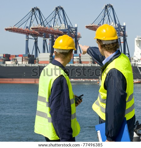 Two dockers in discussion, pointing at the unloading operations of a huge container ship - stock photo