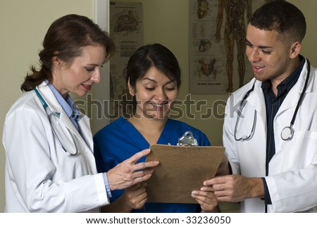Two doctors and a nurse smiling at the information they are reviewing on a clipboard.