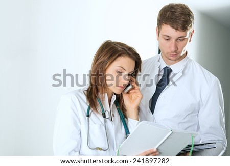 two doctors consulting on telephone at the clinic