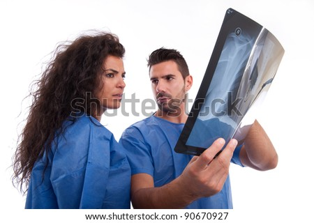 Two doctors looking and discussing an x-ray of a patient