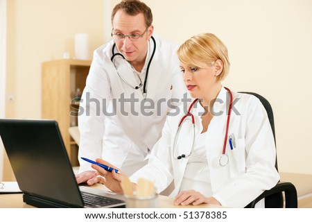 Two doctors - male and female - discussing test reports that show on their laptop screen