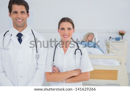 Two doctors smiling and standing in front of a hospitalized patient - stock photo