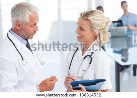 Two doctors speaking to each other in a bright office