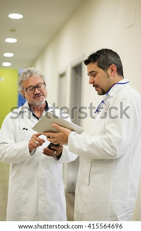 Two doctors talking while looking at pad in hospital hall - stock photo