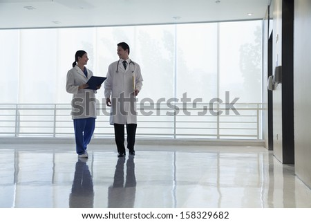 Two doctors walking and smiling in the hospital - stock photo