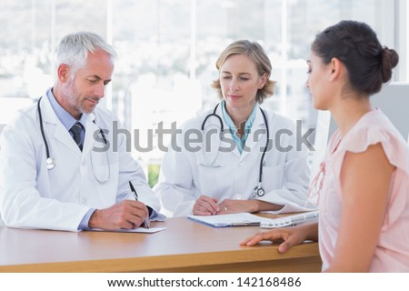 Two doctors with a female patient in a bright office - stock photo