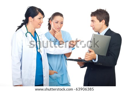 Two doctors women having discussion with a businessman with laptop and pointing to object isolated on white background - stock photo