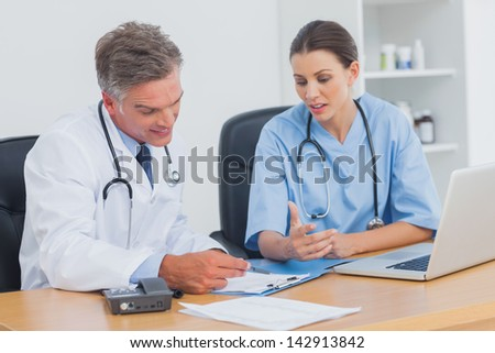 Two doctors working on an important folder in a medical office - stock photo