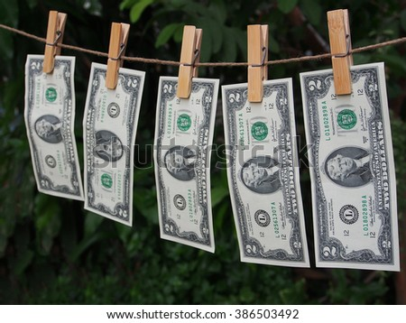 Two dollar bill fixed on clothes peg with green blur backgroung - stock photo