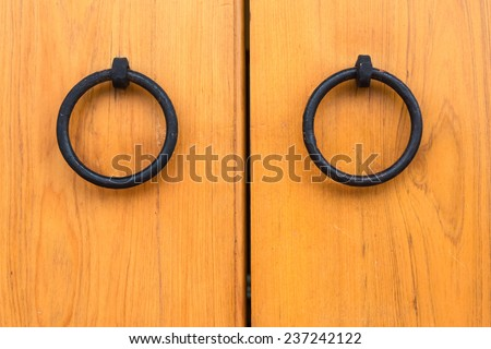 Two Door Knobs of Simple Rings Made of Black Iron  on Yellow Wooden Door of Chinese Style.  - stock photo
