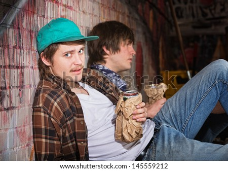 Two drunk young European men sitting outside - stock photo